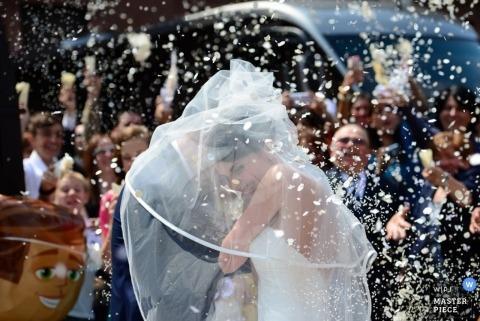 Ein Foto aus Mailand von einem Hochzeitspaar, das sich unter den Schleier der Braut flüchtet, während sie draußen von Gästen mit weißem Konfetti beworfen werden