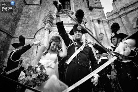 A black and white image from Calabria of a wedding couple passing beneath raised swords with the groom about to hold his own sword aloft while the bride hangs onto her bouquet