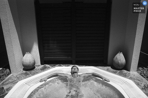 A man relaxing in his enormous frothing jacuzzi in an interesting take on a wedding photograph with huge wooden doors in the background in black and white