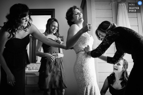 A black and white photo of a last minute adjustment to the waist of the bride's wedding gown in Lombardy while the bride and her bridesmaids share a giggle in her dressing room