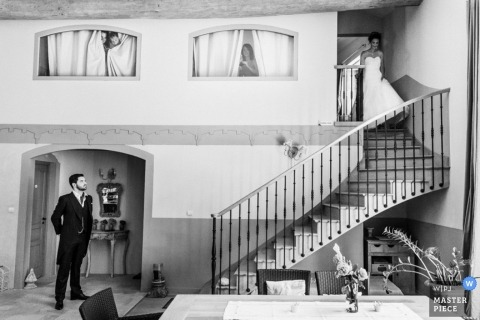 Here comes the bride as she makes her way down to the bottom of the stairs where her groom waits for her in a black and white indoor wedding photograph from Morbihan Brittany