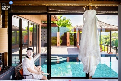 A Phuket bride waits to dress for her wedding with her gown hanging in the doorway to a bright blue pool area setting the scene for a lovely image of destination wedding Thailand