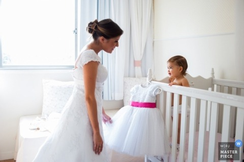 In Brazil a Bahia bride shares a look with her daughter in the nursery, before helping her dress in a puffy white dress with pink ribbon