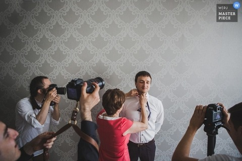 St Petersburg wedding paparazzi pic while the groom gets ready inside a room with silver wallpaper in Russia