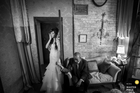 An indoor black and white photo of a tearful CT bride and a reflective groom as they hold hands before their New Haven wedding