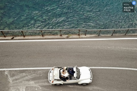 An aerial photo of a VW coupe in Florence Tuscany contains a wedding couple driving down the road with a beautiful water view to the side