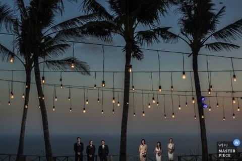 Jakarta Wedding Photographer | Image contains: palm trees, distance shot, sunset, lights, bridesmaids, groomsmen, bridal party, portrait