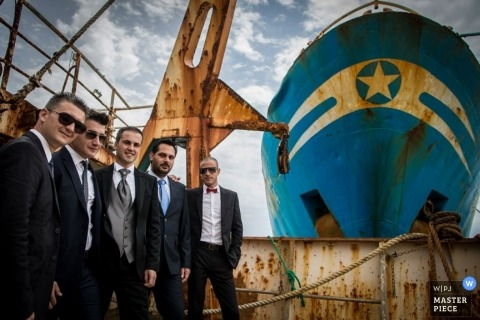 Messina Sicily creative portrait of groom and groomsmen on wedding day with a ship.
