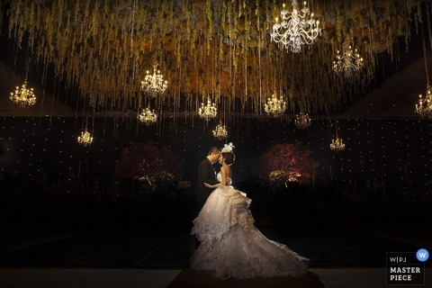 Bali Wedding Photography | Image contains: bride and groom, reception, chandeliers, wedding gown, reception hall, kiss