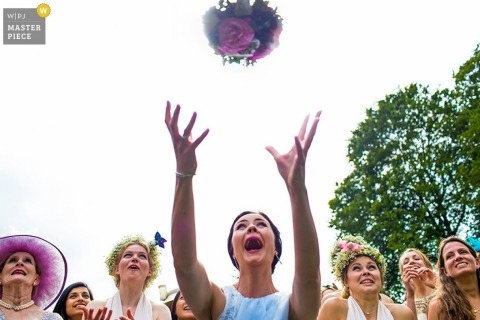 Devon Documentary Wedding Reportage  Image contains: bouquet, flowers, wedding guests, bouquet toss, outdoors