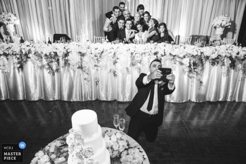 Sydney Documentary Wedding Photography | Image contains:wedding party, selfie, black and white, wedding reception, party, tables, flowers, wedding cake