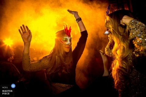 San Diego Wedding Photojournalism | Image contains: dancing, masks, masquerade, orange light, costumes, reception, celebration