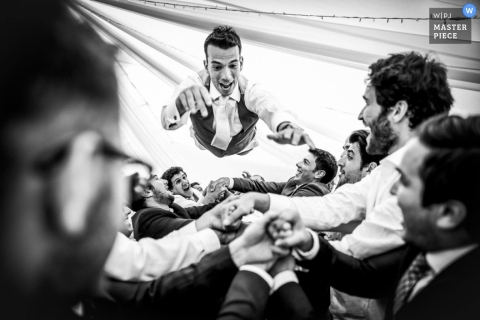 Hertfordshire Wedding Reportage Photography   Image contains: groomsmen, reception, celebration, jumping, tent, black and white