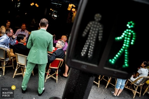 Paris Documentary Wedding Photographer   Image contains: groom, green suit, wedding reception, wedding guests