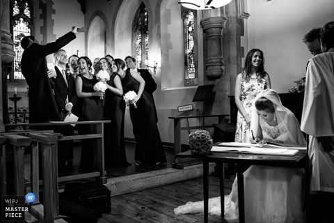 Devon Documentary Wedding Reportage | Image contains: bride, wedding party, black and white, groom, selfie, church, guest book