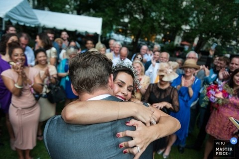 New York City Artistic Wedding Photographer | Image contains: bride, groom, hug, wedding guests, outdoors