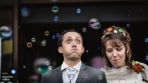 Nouvelle-Aquitaine Wedding Photography | Image contains: bride, groom, bubbles, portrait, leaving the ceremony, outdoors, flowers