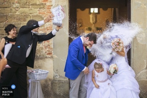 Arezzo Wedding Photography | Image contains: bride, groom, flowergirl, rice, wedding guests, leaving the ceremony