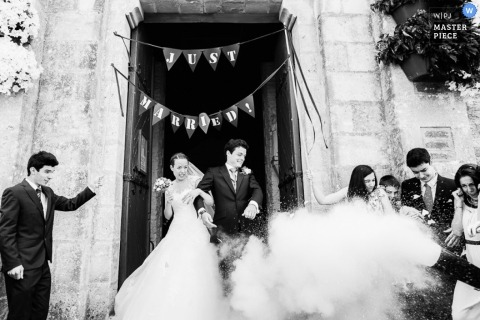 Paris Wedding Photojournalism | Image contains: black and white, bride, groom, leaving the ceremony, confetti, dress, suit, wedding guests, bouquet