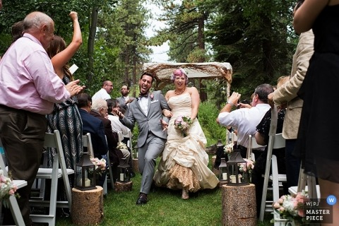 Lake Tahoe Wedding Photography | Image contains: outdoor ceremony, bride, groom, leaving, flowers, cheers, rustic