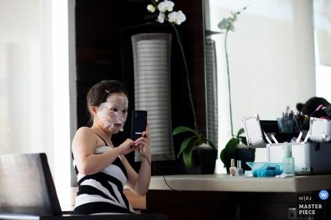 Fotografo di matrimoni documentari di Los Angeles | L'immagine contiene: prepararsi, maschera, selfie camera d'albergo, sposa, fiori