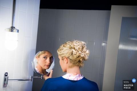 Photojournalisme de mariage primé à Chicago | La mariée se prépare avec un petit miroir de salle de bain.