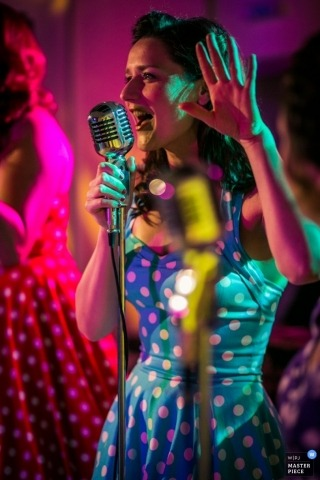 Lisbon Documentary Wedding Photographer | Image contains: singer, performance, polka dot dress, microphone, vintage
