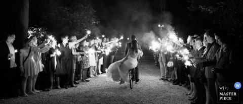 Documentary Wedding Photographer | Image contains: sparklers, black and white, bride, groom, leaving the ceremony, nighttime, wedding guests
