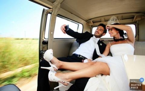 Bari Creative Wedding Photographer | Image contains:bride, groom, van, wedding dress, heels, pasture, selfie, leaving the ceremony