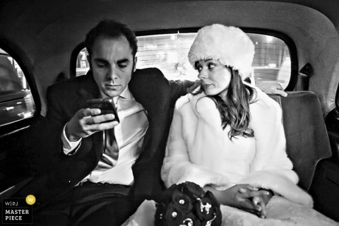 Milan Creative Wedding Photographer   Image contains:black and white, bride, groom, car, phone, hat, leaving the ceremony
