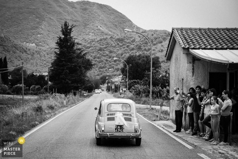 Rome Wedding Photojournalism   Image contains: black and white, classic car, outdoors, wedding guests, mountain