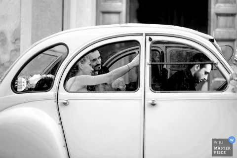Rome Wedding Photojournalism   Image contains: bride, groom, classic car, selfie, black and white, leaving the ceremony