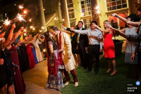 Sacremento Documentary Wedding Photographer | Image contains: bride, groom, kissing, wedding guests, sparklers, outdoors, send off, departure