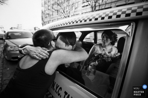 Brooklyn Documentary Wedding Photographer | Image contains: bride, groom, taxi, hugs, city street, bouquet, black and white, emotional