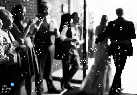 Raleigh Documentary Wedding Photographer   Image contains: bubbles, exiting ceremony, bride and groom, guests, cameras, black and white