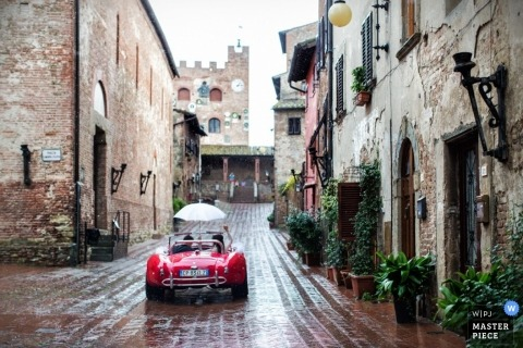 Florence Wedding Photography | Image contains: brick road, brick buildings, red car, rain, umbrella, bride and groom