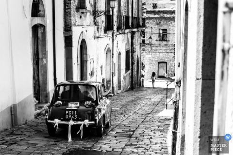 Milan Wedding Photography   Image contains: cobblestone street, buildings, vintage car, leaving ceremony, black and white
