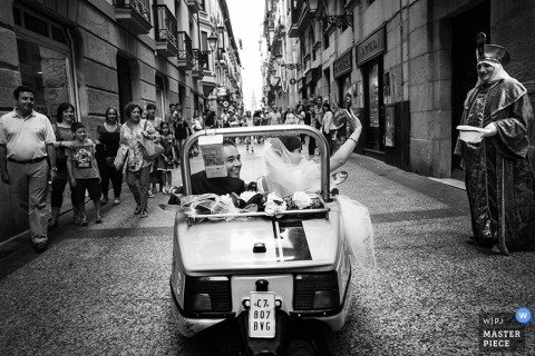 Madrid Wedding Photography | Image contains: vintage car, priest, cobblestone, bride and groom, black and white
