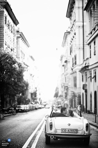 Arezzo Wedding Photography   Image contains: black and white, vintage car, city street, buildings, couple, kissing