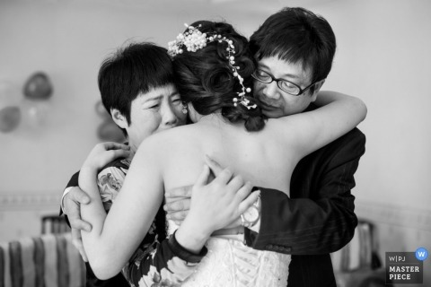 Guangdong Wedding Photojournalism   Image contains: black and white, bride, flowers, father, mother, hug