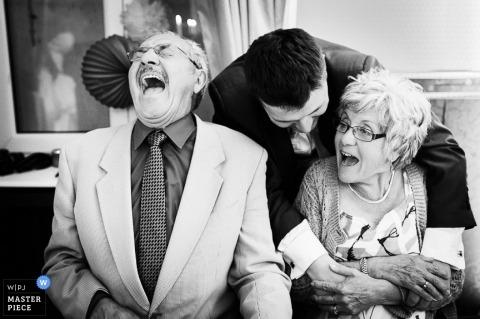 Île-de-France Wedding Photography   Image contains: black and white, groom, parents, laughter, portrait