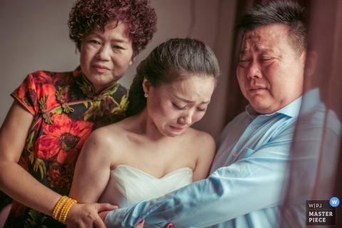 Shanghai Wedding Photography   Image contains: bride, parents, wedding dress, hug, emotional