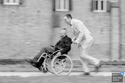 Zuid Holland Wedding Photojournalism   Image contains: black and white, groom, wheelchair, slow shutter, pan, motion, follow
