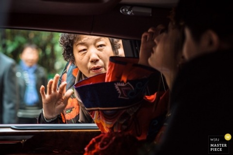 Hangzhou City Wedding Photography   Image contains: bride and groom, car, traditional dress, family, window, ceremony