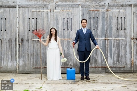 Paris wedding photographer makes an image of the bride and groom holding a rake and a hose for their portrait
