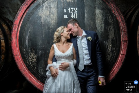 Venice wedding photographer captured this beautiful portrait of the bride and groom standing in front of a giant wine barrel