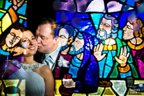 Philadelphia wedding photographer creates an image of the bride and grooms reflection in a stained glass window