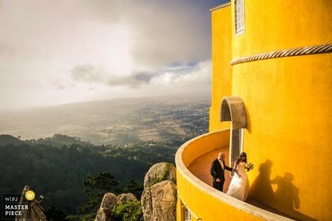 De huwelijksfotograaf van Lissabon maakte dit prachtige afstandsschot van de bruid en bruidegom die het balkon van een groot geel gebouw aflopen