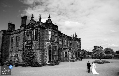 大曼徹斯特婚禮攝影師拍攝了新娘和新郎走進城堡的黑白照片