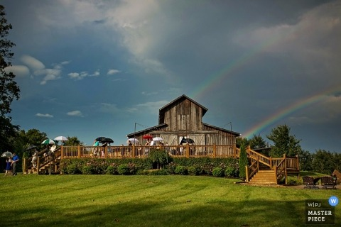Knoxville wedding photographer makes an image of a double rainbow rising above the ceremony site after a rainstorm